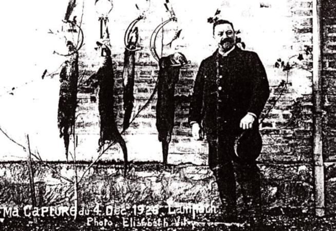 Reproduction d'une photo de P. Lampach posant près de 4 loutres suspendues dans des pièges avec la mention -Ma capture du 4 décembre 1926- rivières Marne, Saulx. Le Pays Vitryat. Mémoires en images.